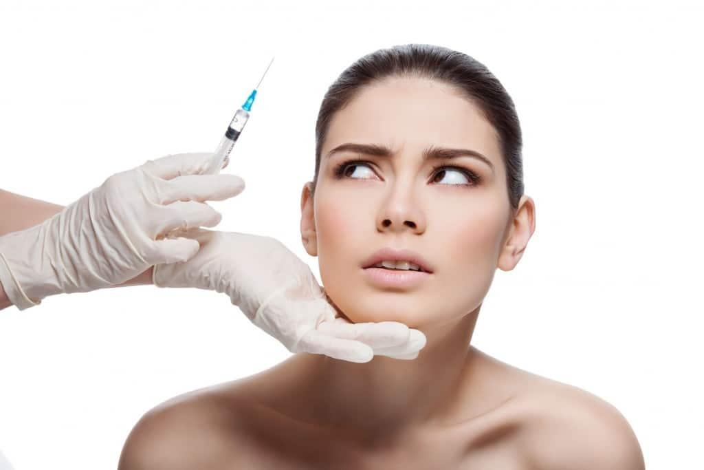 rostro mujer observando jeringuilla miedo al botox