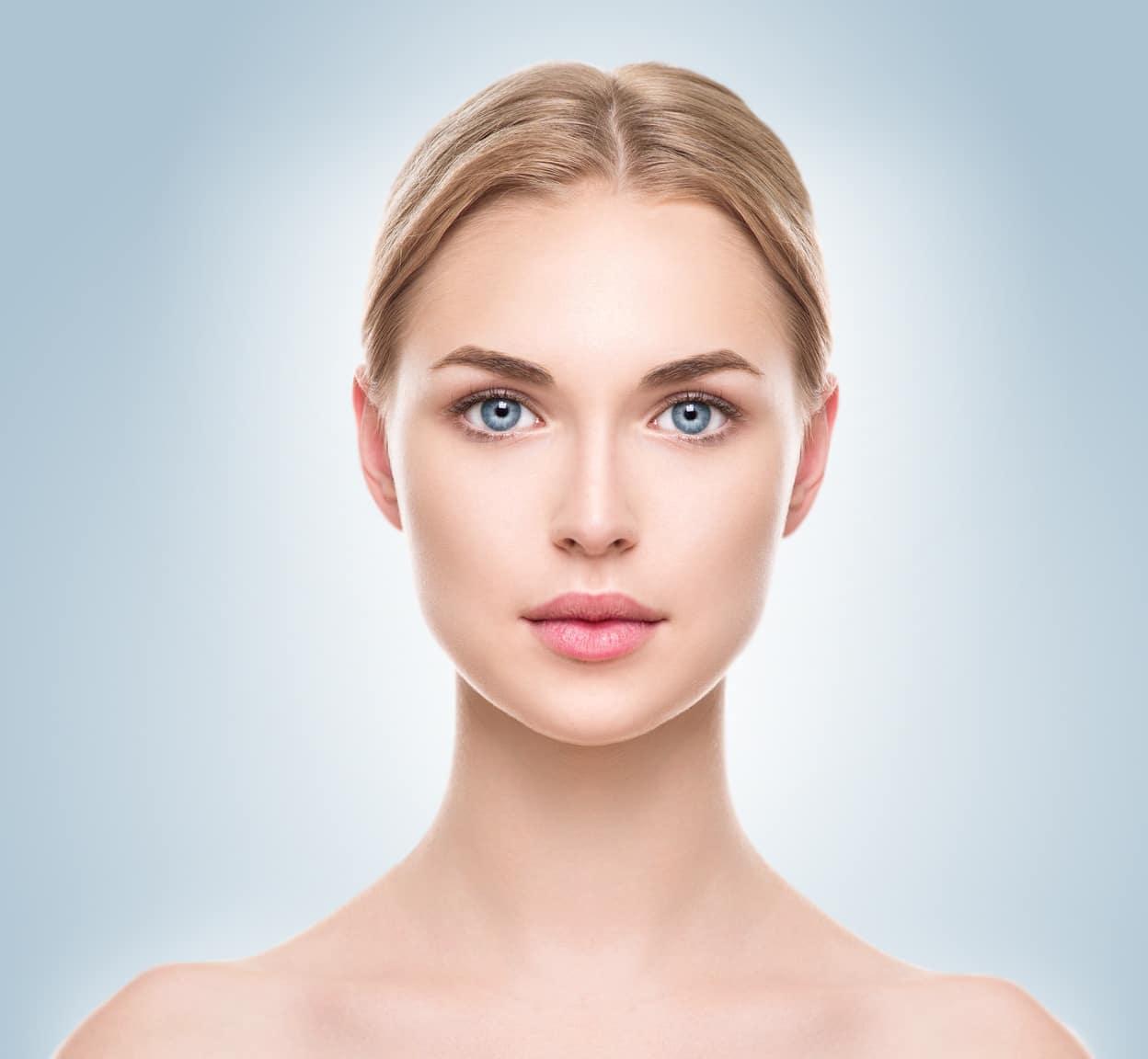 rostro de mujer joven bella sobre fondo azul medicina estetica facial graziella moraes