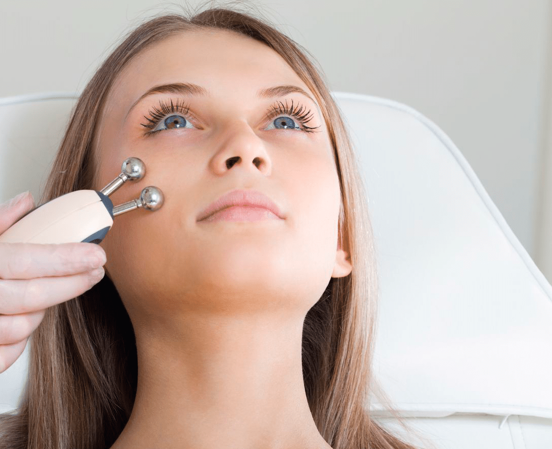 mujer que tiene un tratamiento facial estimulante de un terapeuta
